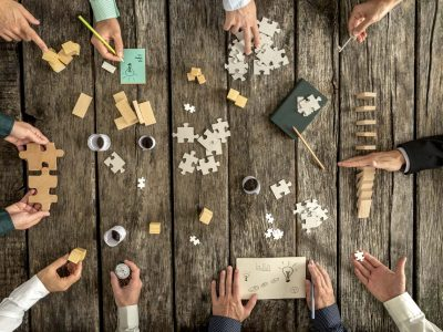 Business planning and brainstorming concept with a team of ten businessmen organizing strategy while holding puzzle pieces, writing down ideas on paper and rearranging wooden blocks, top view.